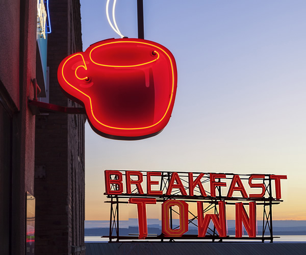 Photo showing illuminated letters and cup signage as part of brand identity for west London brand strategy and communications consultancy, Breakfast Town