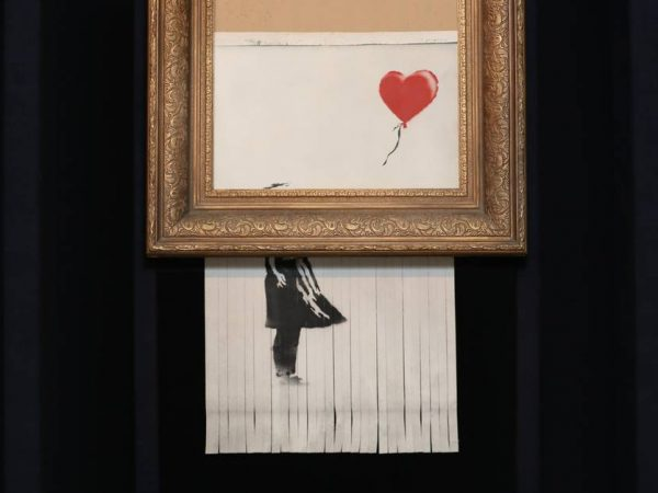 Photo showing how Banksy's Girl With Red Balloon was shredded at auction and increased the value of the creative idea