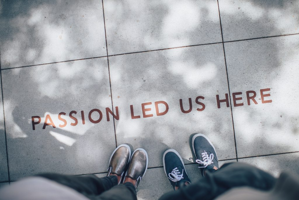 feet on pavement with wording saying 'Passion led us here' to illustrate teamwork in Breakfast Town blog on starting a business and launching a brand